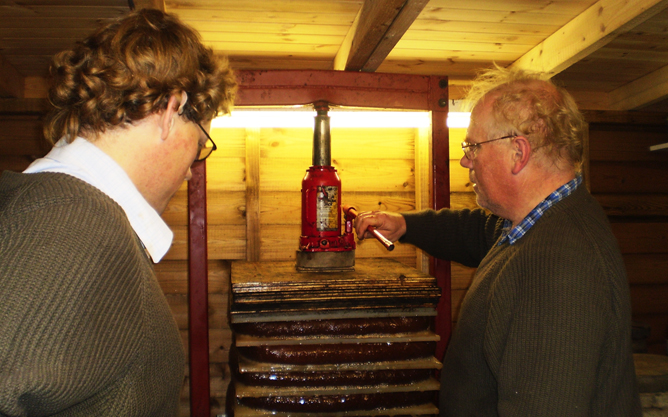 Alan and Richard Stone making cider in their shed.